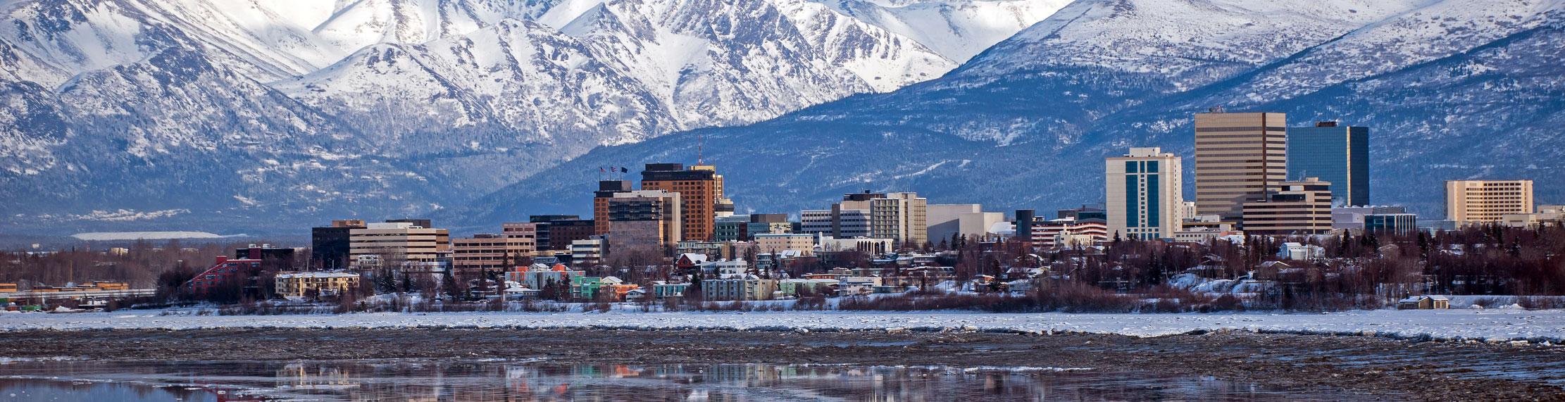 Downtown Anchorage Alaska with mountain backdrop.